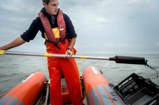 Nederland, Waddenzee, 26-07-'13; Medewerkers en vrijwilligers van het NIOZ (Koninklijk Nederlands Instituut voor Onderzoek der Zee) nemen tussen juli en september bijna 5000 monsters van het bodemleven en het sediment van de droogvallende delen van de Nederlandse Waddenzee. Zo onderzoeken ze de verspreiding van schelpdieren, wormen en kreeftachtigen die het voedsel vormen voor vogels en vissen. Foto: Kees van de Veen